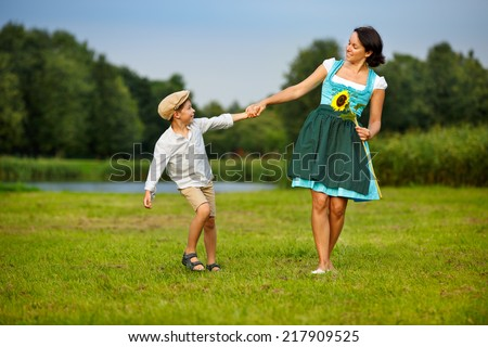 Attractive young woman in a dirndl with her son on meadow - stock photo