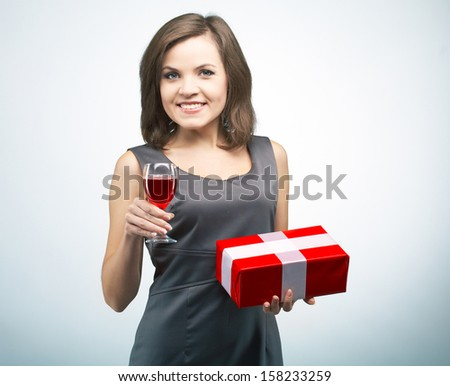 Attractive young woman in a gray business dress. Holding red gift box and glass of wine. On a gray background