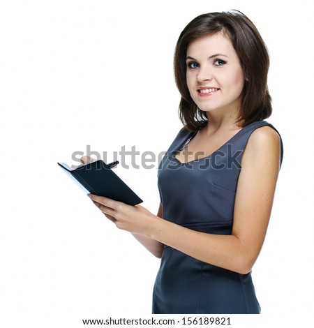 Attractive young woman in a gray business dress. writing in a notebook. Isolated on white background