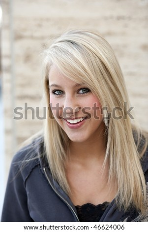 Attractive young woman in a gray hoodie smiles towards the camera while standing outside. Vertical shot. - stock photo