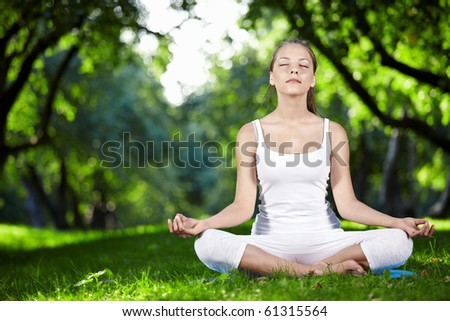 Attractive young woman in a lotus position - stock photo