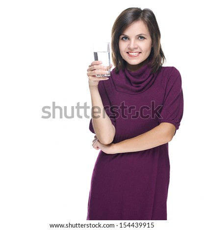 Attractive young woman in a red dress. Holding a glass of mineral water. Isolated on white background