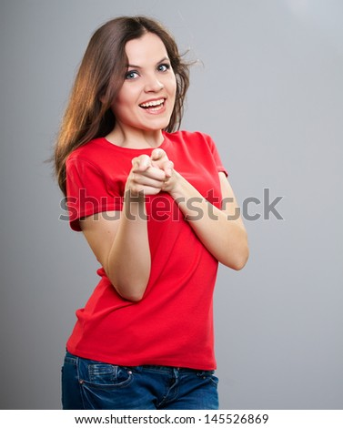 Attractive young woman in a red shirt. Pointing at you with her fingers. On a gray background - stock photo