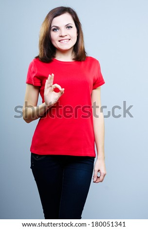 Attractive young woman in a red shirt. Shows sign okay. On a gray background