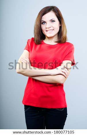 Attractive young woman in a red shirt. Stands with folded hands. On a gray background
