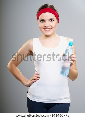 Attractive young woman in a white T-shirt. Woman holding a bottle of mineral water. Isolated on a gray background