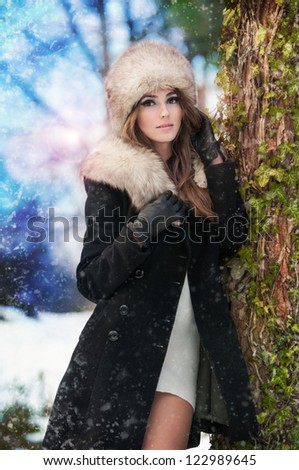 attractive young woman in a winter fashion shot.Winter wild woman on snow.Winter Girl with beautiful make up,  and snow flake, forest background.Portrait of attractive - stock photo