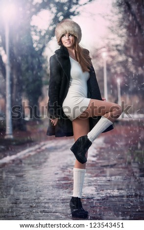 attractive young woman in a winter fashion shot.Winter wild woman on snow.Winter Girl with beautiful make up, and snow flake, forest background.Portrait of attractive woman - stock photo