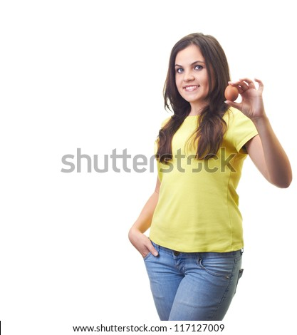 Attractive young woman in a yellow shirt holding in her left hand an egg. Isolated on white background