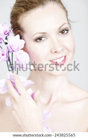 Attractive young woman in beauty style pose holding Orchid flowers to her face - stock photo