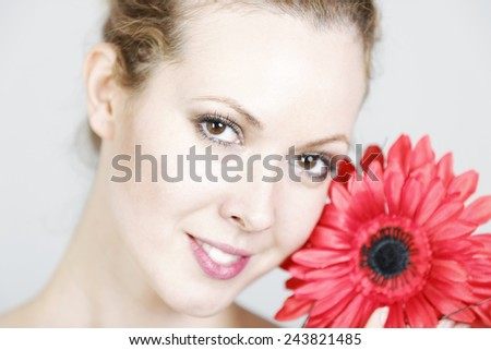 Attractive young woman in beauty style pose holding red flowers to her face - stock photo