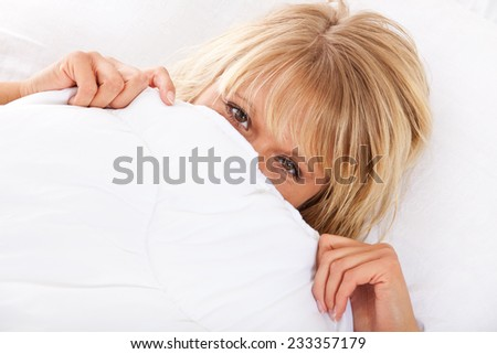 Attractive young woman in bed - stock photo