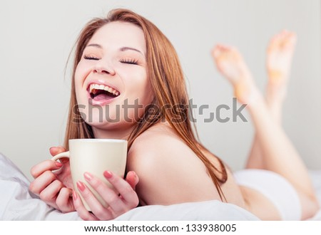 Attractive young woman in bed with a cup of tea