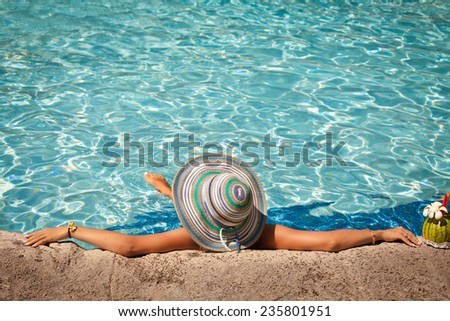 Attractive young woman in big hat relaxing in the swimming pool with exotic cocktail. Girl relaxing at luxury travel resort.