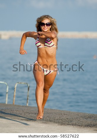 Attractive young woman in bikini is running along the beach