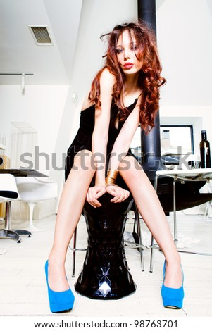 attractive young woman in black dress and high heels shoes sit on chair in modern apartment - stock photo