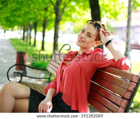 Attractive young woman in black glasses, sitting in a summer park on a bench - stock photo