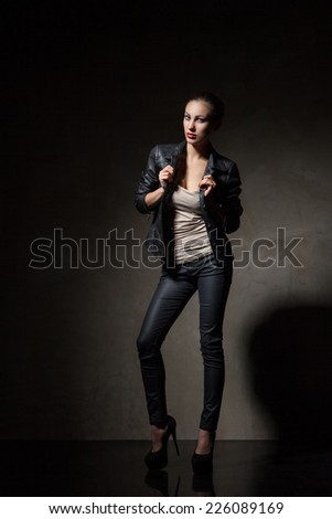 attractive young woman in black leather jacket and pants over dark grey background - stock photo