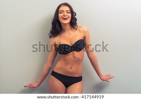 Attractive young woman in black underwear is posing, looking away and smiling, standing against gray background