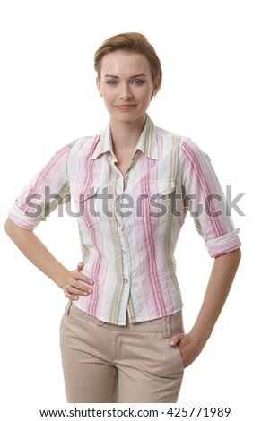 Attractive young woman in casual clothes standing hand on hip, smiling. - stock photo