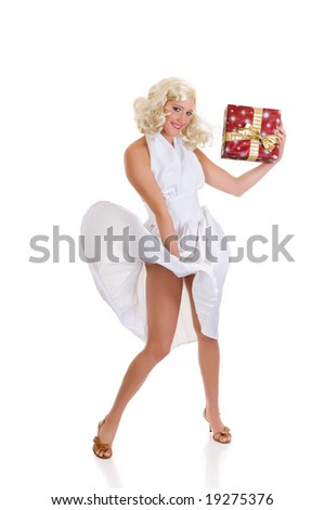 Attractive young woman in classy white dress showing Xmas present.  Marilyn Monroe imitation. Studio shot, white background.