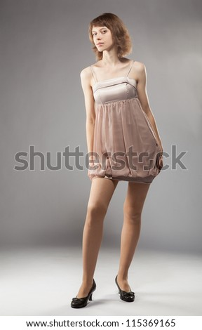 Attractive young woman in dress posing in studio