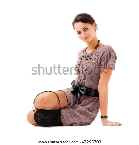Attractive young woman in dress sitting on a white background with copyspace