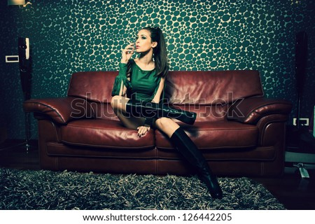 attractive young woman in green dress and long boots sit and smoke in retro style living room - stock photo