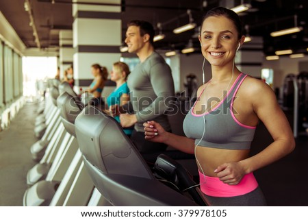Attractive young woman in headphones running on a treadmill in gym, looking at camera and smiling - stock photo