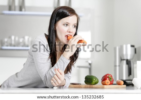 Attractive young woman in her elegant kitchen eating a raw carrot. - stock photo