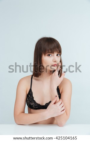 Attractive young woman in lingerie sitting at the table and looking at camera isolated on a white backround - stock photo