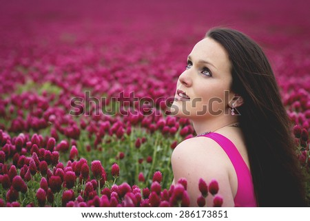 Attractive Young Woman In Pink Clover Field Looking Up - stock photo
