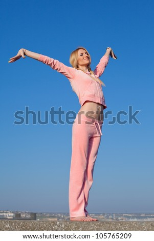 Attractive young woman in pink sportswear posing on background of sky. Barefoot girl with hands raised on open air