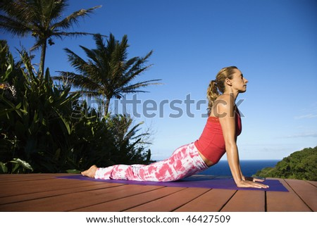 Attractive young woman in red practices yoga on a deck with the ocean in the background. Vertical shot. - stock photo