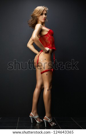 Attractive young woman in red sexual lingerie on dark background - stock photo