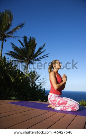 Attractive young woman in red sits on an exercise mat doing yoga with the ocean in the background. Vertical shot. - stock photo