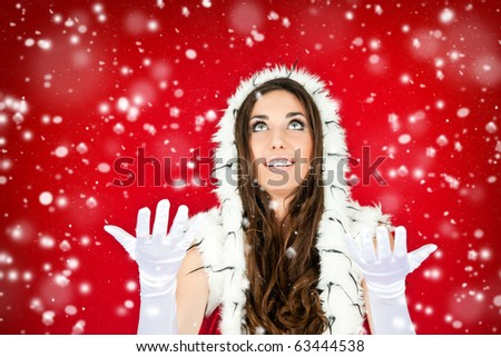 attractive young woman in santa clothes standing in the snow - stock photo