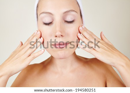 Attractive young woman in spa putting skin lotion on her face - stock photo