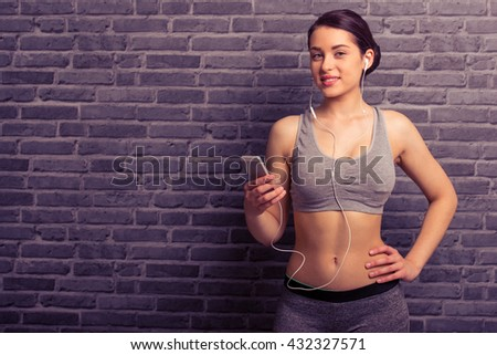 Attractive young woman in sportswear and earphones is listening to music using a smartphone, looking at camera and smiling, against brick wall - stock photo