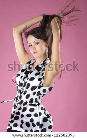 Attractive young woman in the dress against pink background - stock photo
