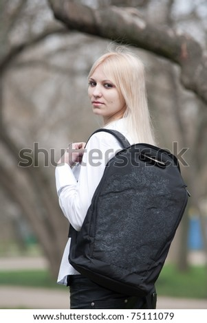 Attractive young woman in the park. Blonde with backpack looking at camera - stock photo