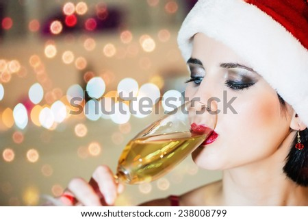 Attractive, young woman in the Santa Claus costume drinking champagne. Bokeh background, shallow doff, head shot, copy space - stock photo