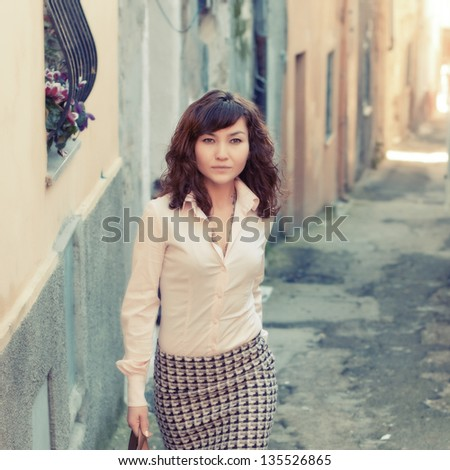 Attractive young woman in the small italian city, retro style