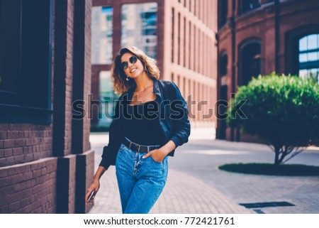 Attractive young woman in trendy apparel and sunglasses enjoying walk in old town, charming hipster girl dressed in stylish outfit strolling on street passing city architecture and buildings