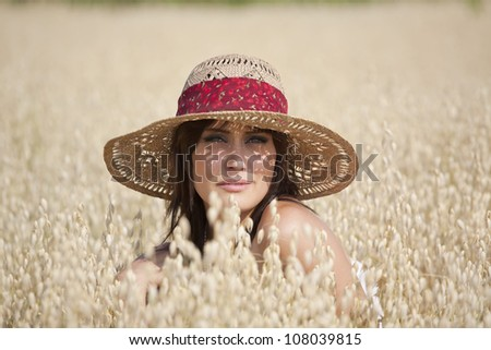 Attractive young woman in wheat grass field posing for portrait with straw hat on. - stock photo