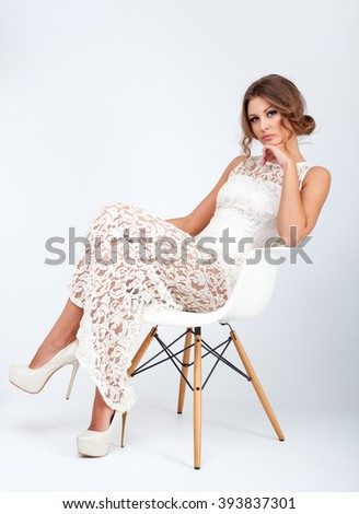 Attractive young woman in white dress sit on the chair. Vertical Studio photo - stock photo