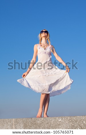 Attractive young woman in white posing on open air. Girl holding her skirt looks up - stock photo