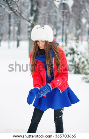 Attractive young woman in wintertime outdoor. Cheerful girl wears blue mittens. - stock photo