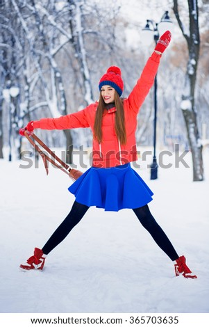 Attractive young woman in wintertime outdoor. Happy and cheerful girl in a red jacket and blue skirt. - stock photo