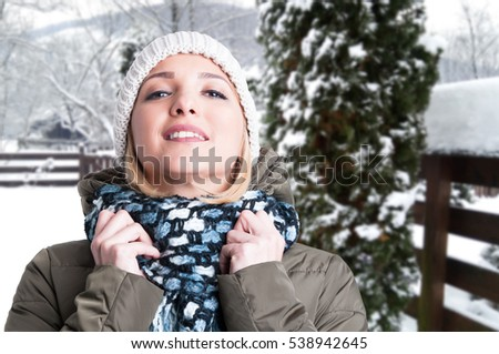 Attractive young woman in wintertime outdoor relaxing in the snow with advertising area